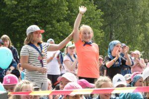 Iloinen partiolainen nostaa kätensä ylös kaverin kanssa
