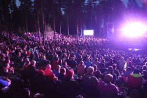 Partiolaiset yhteisohjelmassa pimeässä metsässä, lavalta tulevat valot säteilevät liilaana