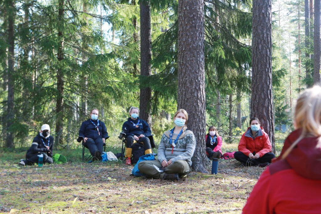 Scotus sitting in forest with face masks.