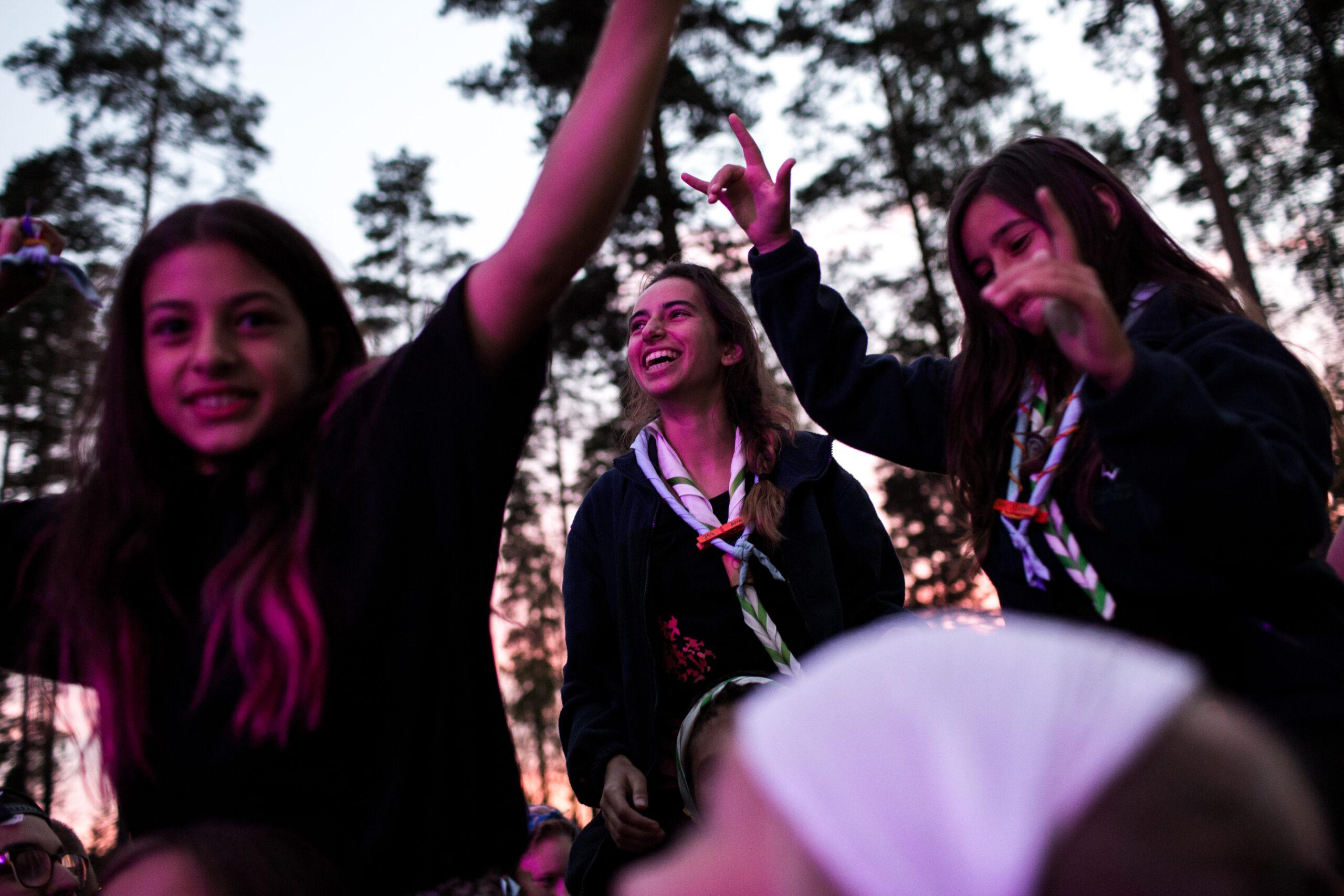 Kolme iloista partiolaista tanssimassa iltahämärässä