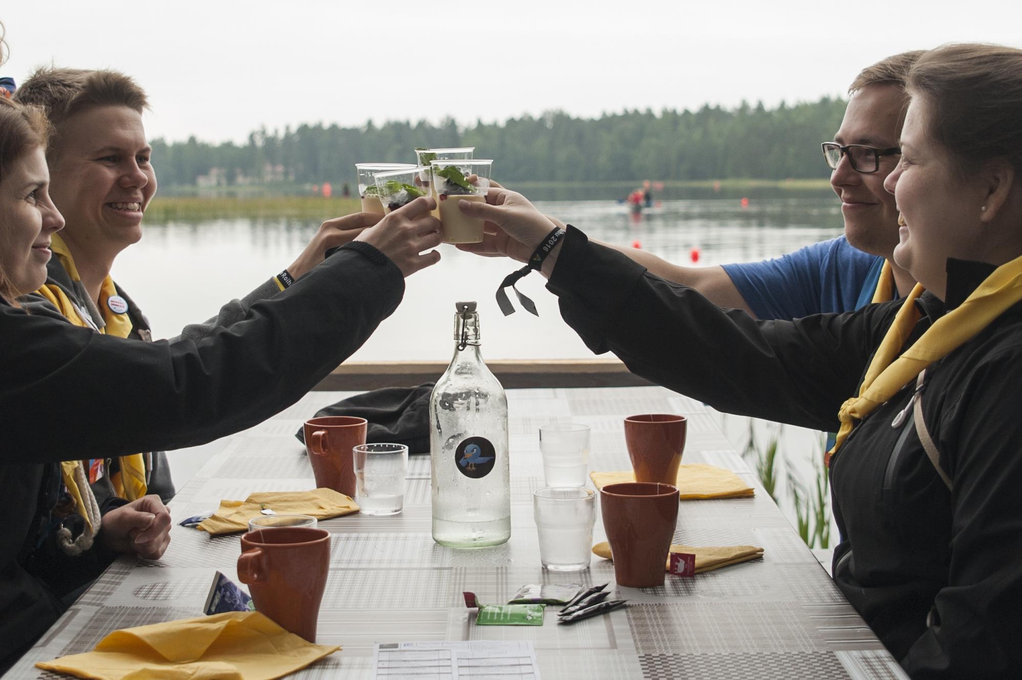 4 iloista aikuista partiolaista skoolaa järven rannalla ravintolassa