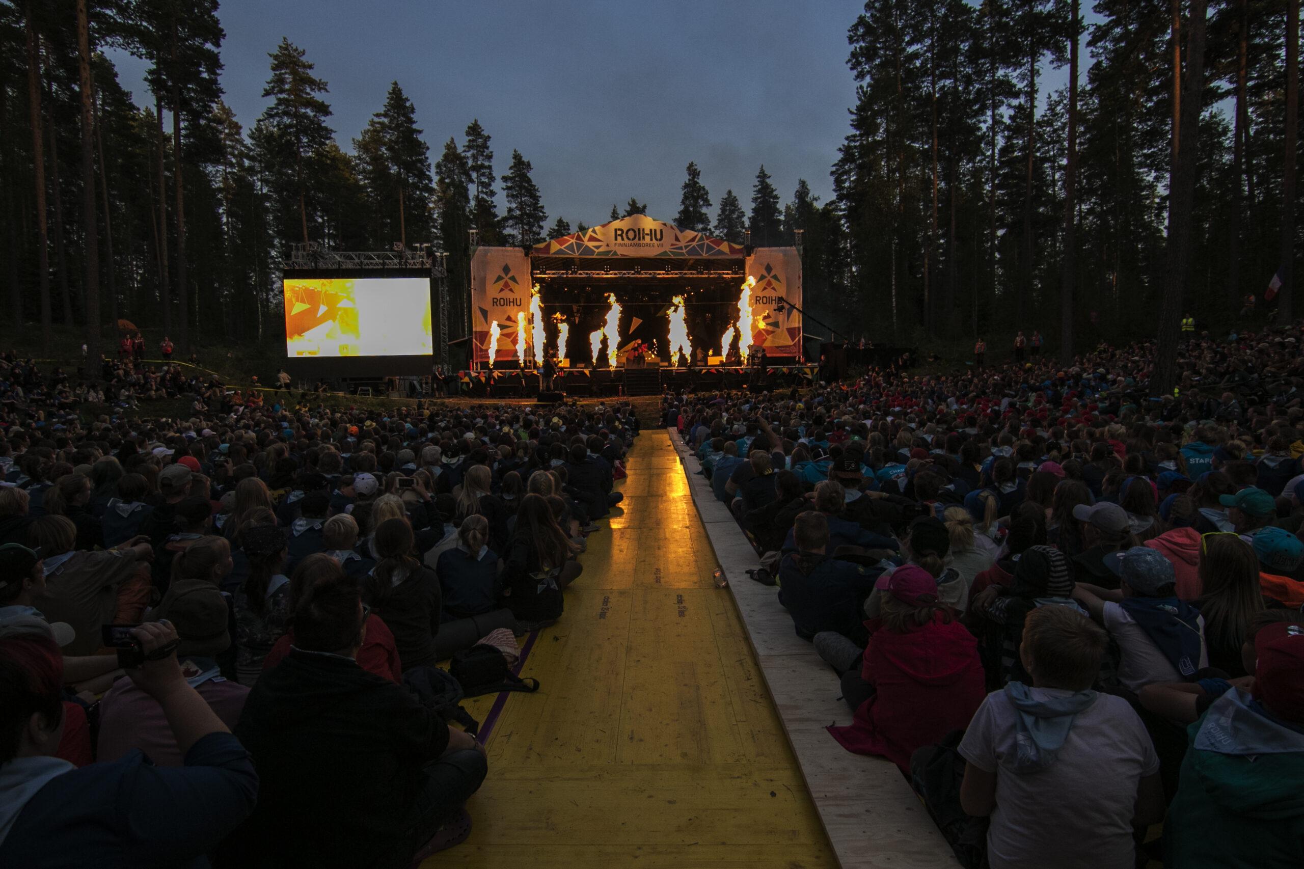Tuhatpäinen Roighun yleisö lavan edessä, lavalla tulilieskoja iltahämärässä